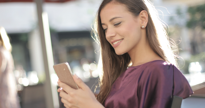 Young woman looking on her phone, outside